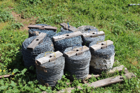 9 ROLLS OF BARB WIRE, SOME PARTLY USED.